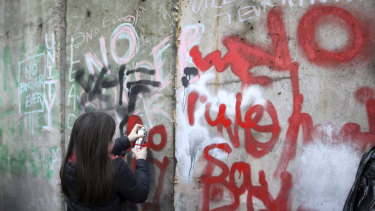 A young demonstrator spray paints on a 'mock' wall on the Northern Ireland-Ireland border near Newry.