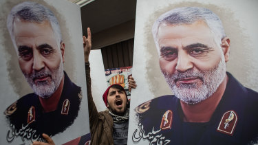 People hold posters of Iranian Revolutionary Guard Major General Qassem Soleimani and during a protest outside the US Consulate in Turkey on Sunday.