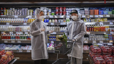 Beijing residents wear protective clothing as they shop for groceries.