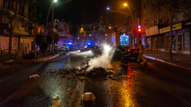 Firefighters extinguish a fire lit by rioters in Haifa, Israel.