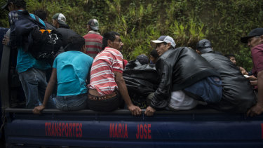 Migrants from Honduras ride on a truck tray towards the Mexican border, in Cocales, Guatemala.