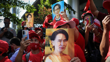 People hold up images of Myanmar's de-facto leader Aung San Suu Kyi at a protest outside Maynmar's embassy in Bangkok, Thailand.
