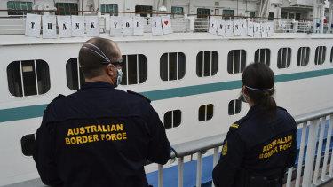 Australian Border Force officers watch the Artania as it departs Fremantle.