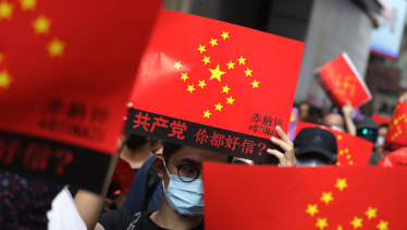 Demonstrators holding signs featuring a swastika made up of yellow stars against a red background march along Hennessy Road during a protest in the Causeway Bay district of Hong Kong.