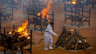 A man performs the last rites for a COVID-19 victim at an old granite quarry repurposed into a crematorium in Bengaluru, India.