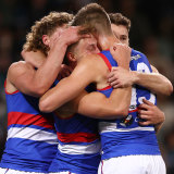 Roarke Smith's teammates get around him after a goal against Port Adelaide in the preliminary final.