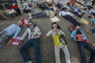 Young demonstrators, with their eyes blindfolded, lie down in the street on Tuesday in Yangon.
