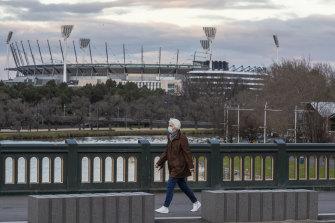 A woman wearing a mask walks along a bridge as she walks past the MCG in August.