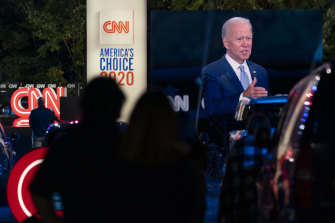 Audience members watch from their cars as Democratic presidential candidate former vice-president Joe Biden, seen on a monitor, speaks during a CNN town hall in Moosic, Pennsylvania.
