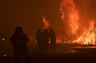 Safety issues: A firefighter is assisted seconds after being hit in thick smoke as fire roared through eastern Bilpin in the Blue Mountains in December.