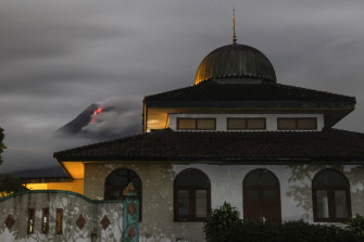 Hot lava runs down from the crater of Mount Merapi, partially seen behind a mosque in Sleman, Indonesia.