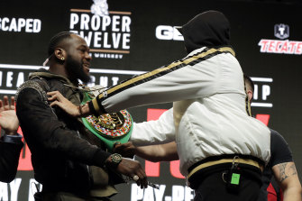 Deontay Wilder and Tyson Fury shove each other during their press conference.