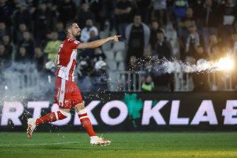 Milos Degenek carries a flare off the field during last year's Serbian Cup semi-final.