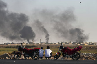 People in Akcakale Sanliurfa province, south-eastern Turkey, watch smoke billowing inside Syria.