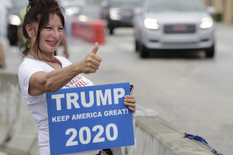 A supporter gives a thumbs-up as she waits to see the motorcade carrying US President Donald Trump pass by on his way to Mar-a-Largo.