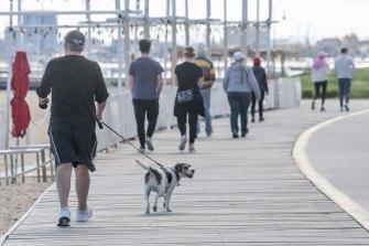 People enjoy some fresh air and a walk on St Kilda beach on Wednesday.