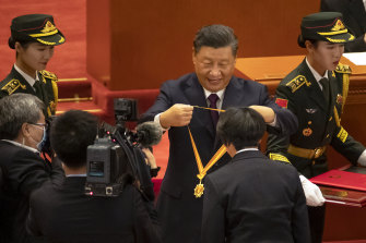 Chinese President Xi Jinping presents a medal at an event to honour some of those involved in the fight against COVID-19 at the Great Hall of the People in Beijing on Tuesday.