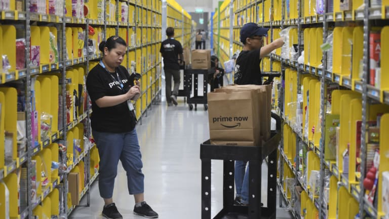Staff collect merchandise for customers' orders from shelves at the newly-opened Amazon Prime Now facility in Singapore.