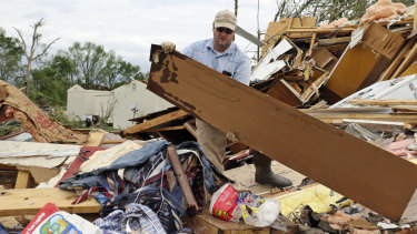 Roman Brown moves part of a wall out of his way in a friend's destroyed home outside of Hamilton, Mississippi, on Sunday.