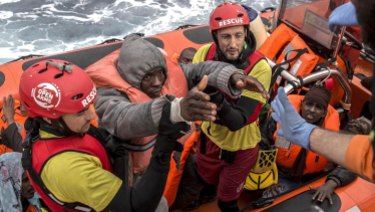 Refugees and migrants are transferred to a rescue ship by aid workers of the Spanish NGO Proactiva Open Arms, in February.