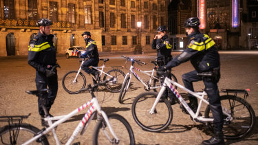 Police patrol the streets of Amsterdam ahead of a curfew.
