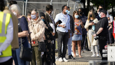 People queue at a walk-in COVID-19 testing centre in Bolton, in northern England.