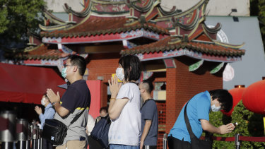 People wear face masks to protect against the spread of the coronavirus and pray outside Hsing Tian Kong Temple in Taipei, Taiwan.