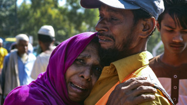 'They are taking us forcefully': a Rohingya man comforts a refugee woman as they are relocated to Bhasan Char.