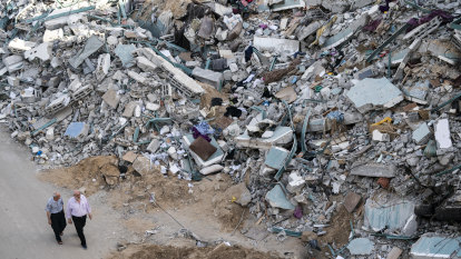 Children make grim game of climbing over rubble of homes