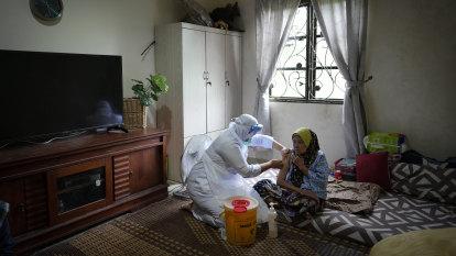 Amid political turmoil, Malaysia directs vaccine surge at virus hotspot