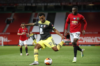 Ryan Bertrand of Southampton shoots under pressure from Aaron Wan-Bissaka of Manchester United during the Premier League match between Manchester United and Southampton FC at Old Trafford.