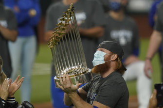 Justin Turner, who was pulled in the eighth inning after testing positive for coronavirus, celebrates with the trophy.
