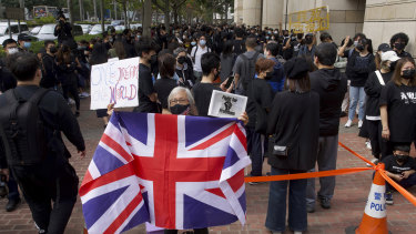A woman holds a British flag as supporters queue up outside a court to try to get in for a hearing in Hong Kong on Monday.