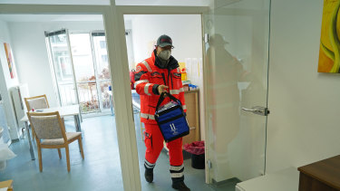 A German Red Cross worker carries a thermo container to pick up the Pfizer-BioNTech COVID-19 vaccine at a nursing home in Grossraeschen.