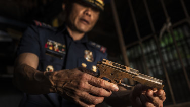 Col. Jaime Quiocho holds a confiscated gun part made by illegal gunsmiths in Danao.