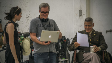 Luke Davies, centre, and George Clooney, right, enjoy a lighter moment in a script reading on Catch-22.