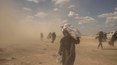 A woman carries supplies from the reception area.