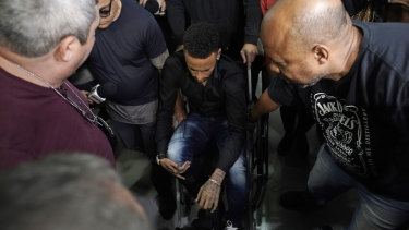 Brazilian soccer player Neymar arrives to a police station, in a wheelchair due to an ankle injury, in Rio de Janeiro, on THursday. Polcie say he will testify soon.