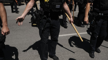 Police in riot gear stand guard during duelling protests outside of the Louisville Court House in Louisville, Kentucky.
