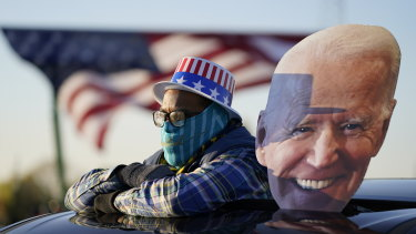 A Democrat supporter watches Joe Biden address a rally in Michigan on Saturday.