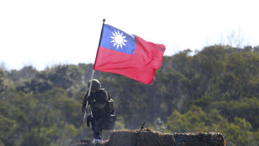 A soldier holds a Taiwanese flag during a military exercise aimed at repelling an attack from China in Hsinchu County, northern Taiwan.