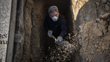 An undertaker prepares a grave for the burial of a victim of the COVID-19 at the Almudena cemetery in Madrid on Saturday.
