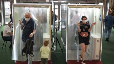 People wearing face masks and gloves to protect against coronavirus come through passages equipped with disinfectant sprays at a shopping mall entrance in Moscow, Russia.