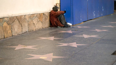 A person sits near stars on the Hollywood Walk of Fame in Los Angeles. California experienced the sharpest rise of homelessness of any state last year.