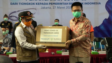 Chinese and Indonesian officials pose with aid supplied by China as it arrives in Jakarta.