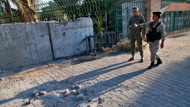 Security forces inspect the scene of the rocket attack at the gate of al-Zawra public park in Baghdad, Iraq in November.