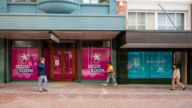 Pedestrians walk past empty shops in Wellington in late August.