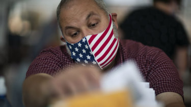 Election inspector Ron Takala processes ballots as the counting of absentee votes begins at City Hall in Warren, Michigan.