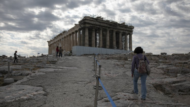 An employee of the Greek Culture Ministry walks alongside a belt separating visitors into sections at the archaeological site of the Acropolis in Athens.