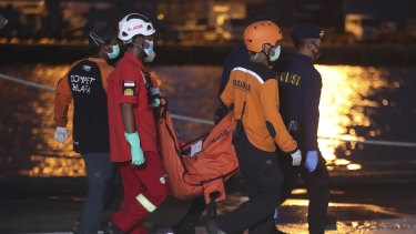 Indonesian rescue and police teams carry debris recovered from the crashed Sriwijaya Air passenger jet on Wednesday.